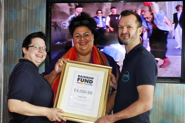 Maria Baker (centre) a member of the Rainbow Fund grants panel hands Legends managers, Jemela Quick (left) and Dan Austin (right) a certificate of thanks for £4,060.69 raised on Pride Sunday.